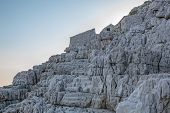 foto of stone house  - Old stone fishing houses on the rocks at sunset - JPG