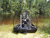 stock photo of airboat  - airboat parked on marsh bank cooling off and pointing in the marsh - JPG