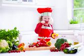 stock photo of vegetarian meal  - Kids cooking fresh vegetable salad in white kitchen - JPG