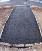 stock photo of distortion  - The fresh black just laid asphalt at the road with wide angle distortion view - JPG