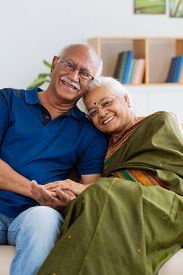 foto of indian  - Portrait of senior Indian couple smiling and looking at the camera - JPG