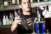 Barman with shaker making cocktail. Focus on bottles and glass.