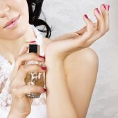 Bride spraying perfume on her wrist. Focus on hand with perfume bottle.