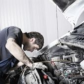 stock photo of car repair shop  - auto mechanic repairing a car engine - JPG