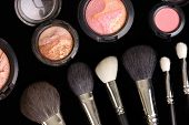 makeup brushes and blusher on black