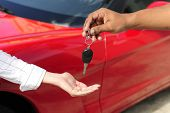 car dealership: woman receiving car key from salesman poster