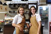 Two happy waitresses working at a cafe