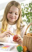 Little girl painting easter egg