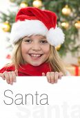 Pretty blond hair girl with santa hat and red comforter holding white board with space for text isol