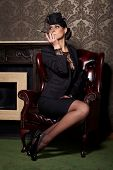 Glamorous brunette woman holding cigarette in mouthpiece sitting in old fashioned chair near fireplace