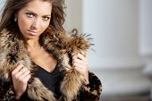 Portrait of pretty female in fashionable coat posing during photoshoot