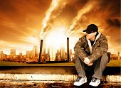 Skater sits in front of a polluted city