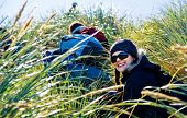 Attractive girl hiking through tussock grass