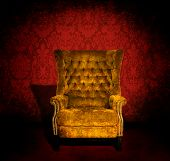 A grungy gold velvet chair in a dark room with red Victorian wallpaper