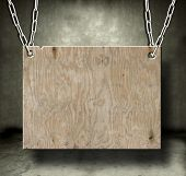 Old piece of wood hanging from chains in a grungy room