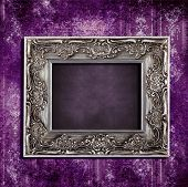 Intricate old frame hanging on grungy violet vintage wallpaper