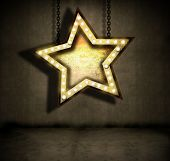 grungy star sign with marquee lights hanging by chains