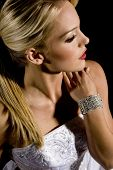 Beautiful bride against a black background wearing a diamond bracelet