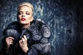Beautiful woman in luxurious fur coat posing in studio. Luxury, rich lifestyle. Fashion shot.  poster