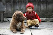 ANNAPURNA, NEPAL - MARCH 20: An unidentified young baby pets her dog in her village on March 20, 2008 in Nepal.