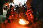 DELHI - FEBRUARY 11: Men sitting around street fire at night on February 11, 2008 in Delhi, India. Winters can get quite cold in the desert capital.