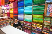 DELHI - JAN 15: Shopkeeper sitting in front of shelves of colourful fabric on January 15, 2008 in De