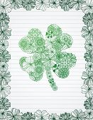 Shamrock made of flowers on lined paper.