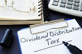 Dividend Distribution Tax Ddt Written On A Sheet Of Paper. poster