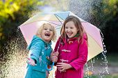 Kids With Umbrella Playing In Autumn Shower Rain. poster