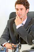 Portrait Of Thoughtful Modern Businessman In Office