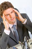Portrait Of Stressed Modern Businessman Sitting At Office Desk