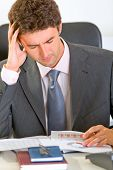 Stressed Modern Businessman Sitting At Office Desk And Working With Documents