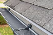 Plastic Guard Over New Dark Grey Plastic Rain Gutter On Asphalt Shingles Roof At Shallow Depth Of Fi poster