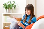 Teenager girl home - student write homework sitting on sofa