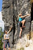 Rock climbing male instructor hold rope blond woman sunny day
