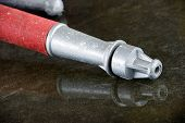 foto of firehose  - A nozzle on the wet floor in a firestation used by firefighters - JPG
