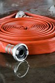 stock photo of firehose  - A rolled up firehose on the wet floor in a firestation used by firefighters