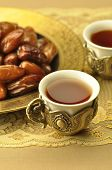 A rich, golden set of arabic  tea cups and dates
