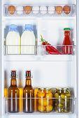 Eggs, Bottles Of Milk And Preserved Vegetables In Fridge poster