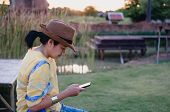 Asian Woman Wear Hat Sitting Outside Use Mobile Phone At Garden With Chill Out Feeling.relax Leisure poster
