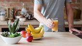 Healthy Eating Habit. Unrecognizable Man Holding A Glass Of Freshly Squeezed Fruit Juice. Natural Or poster