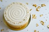 Cake With White Cream, Decorated With Silver And Gold Confectionery Sprinkles And Gold Leaf On A Whi poster