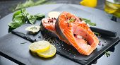 Salmon. Raw Trout Red Fish Steak served with Herbs and Lemon and olive oil on slate. Cooking Salmon, poster