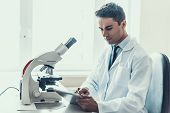 Young Scientist Doing Research In Laboratory. Male Researcher Wearing White Coat Sitting At Desk Nex poster