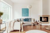 Turquoise Blue Knot Pillow On A Beige Corner Sofa And An Abstract Poster On A White Wall In A Modern poster