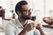 Young Handsome Man With Cup Of Coffee In Cafe. Portrait Of Smiling Bearded Man Wearing Glasses Relax poster