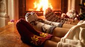 Young Family Wearing Warm Woolen Socks And Lying Under Blanket Relaxing At Fireplace poster
