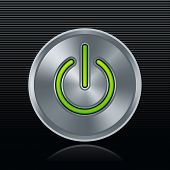 Round metal start button with green light on dark background