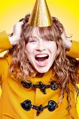 image of overjoyed  - Crazy and overjoyed party girl in a gold party hat laughing in merriment as she runs her hands through her wavy blonde hair - JPG