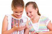 stock photo of pre-adolescent girl  - Two girls play with the iPhone - JPG